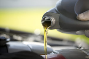 Fresh oil pouring into a car engine during a service